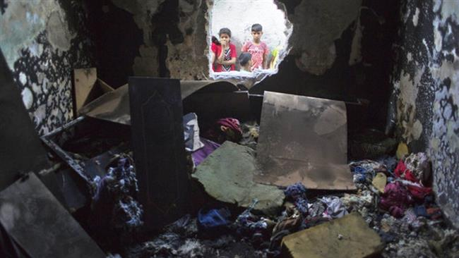 Palestinian children look through a hole in a wall at a burned bedroom where three children were killed by candle sparked on their family house in the Shati refugee camp in Gaza City, Saturday, May 7, 2016. Source: PressTV.