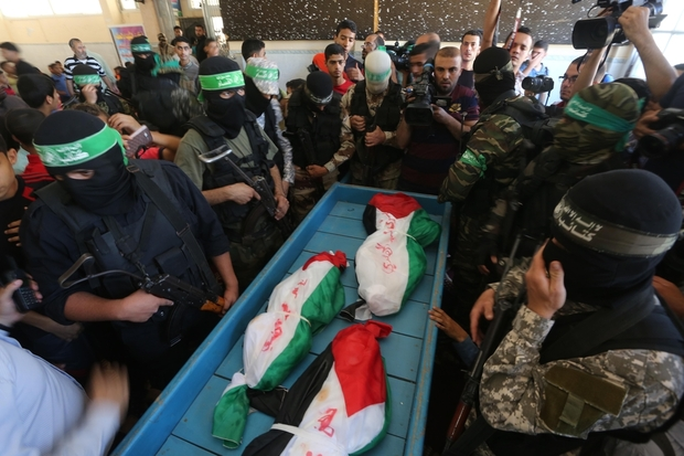 The bodies of the three children surrounded by members of Hamas's al-Qassam Brigades prior to their funeral on Saturday (Mohammed Asad/MEE).
