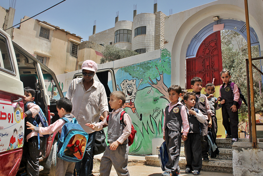 Salwa is orgnizing the kids' movment to the bus, in order to drive them home. Credit: Asmaa Elkhaldi/The Turban Times
