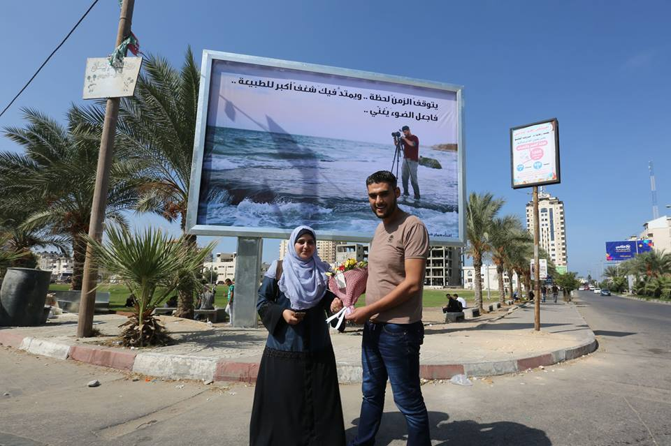 Samah Shamali, and Mahmoud Abu Hamda stand in front of the board of her husband.