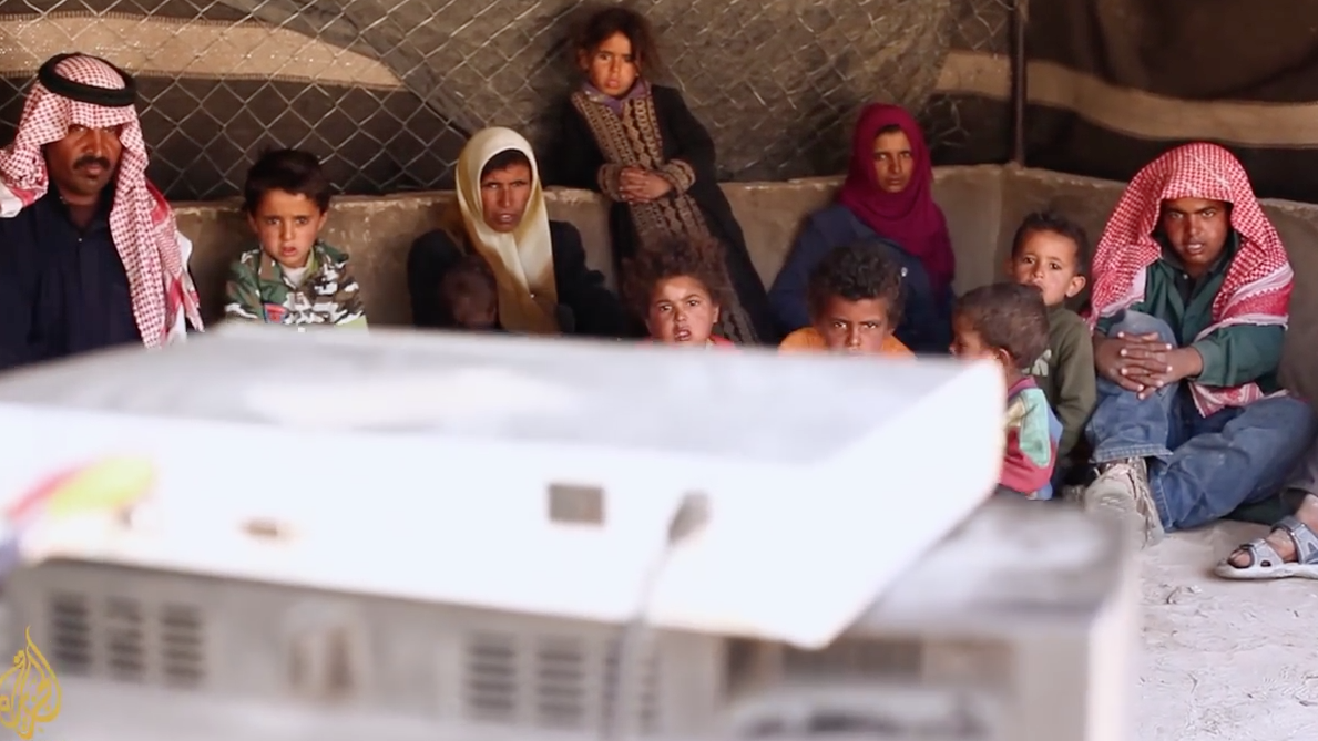 "After starting the generator and setting up their TV and receiver, a Bedouin family in Petra watches television together. Screenshot from a video by Al-Jazeera: ""The Bedouin of Petra""."